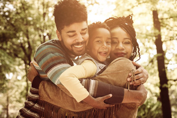 African American family hugging in park.