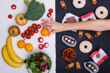 Concept photo of healthy and unhealthy food. Fruits and vegetables vs donuts,sweets and burgers