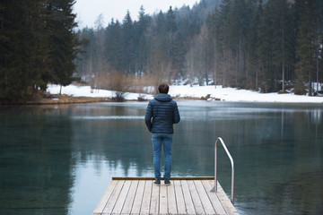 Back view of a man stands on wooden pier at cold winter seasonal lake.