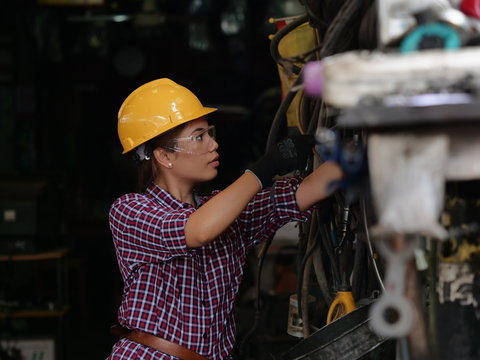 Asian woman working in industry with machine