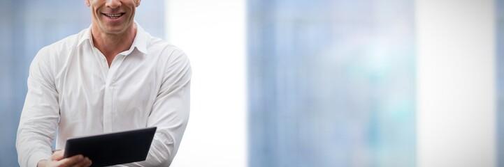 Composite image of portrait of businessman using digital tablet