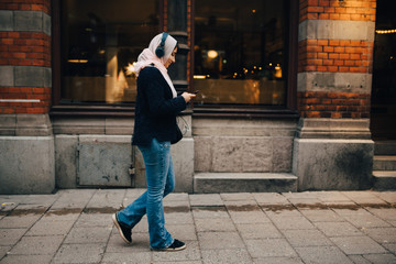 Full length side view of teenage girl walking on sidewalk listening to headphones while using smart phone in city