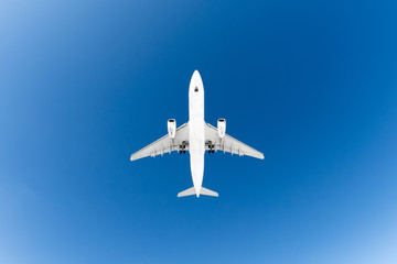 Passenger airplane. View exactly from below, white silhouette against the blue sky.