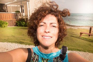 An brunette woman taking selfie portrait outdoor sea side