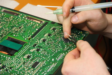 The hands of the master hold a tweezer with a chip and a syringe with flux solder over the PCB