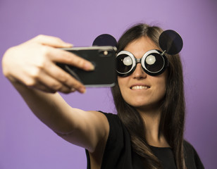 Young Woman Make Selfie in Black Mouse Sunglasses on Purple Background. Photo in Googles on the Latest Smartphone