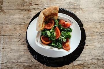 Ein Vegetarisches köstliches Salat mit einem Pizzastück daneben