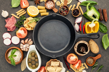 Italian food cooking ingredients on dark stone background with  cast iron pan flat lay and copy space. Wall mural