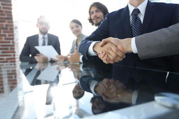 handshake business partners at the meeting.