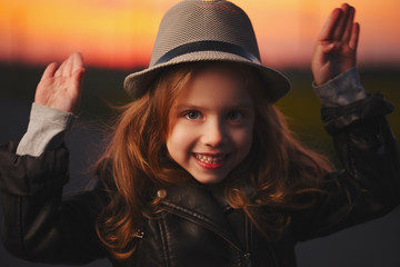 beautiful girl with hat on evening sunset