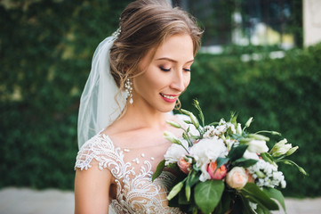 A beautiful bride with a chic bouquet in a lace dress is standing in a green garden. Bride against a background of green ivy in the windows. Portrait of a bride close-up.