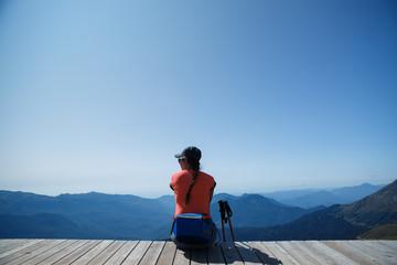 Image from back of brunette on edge of wooden bridge