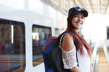 Photo of smiling woman tourist in cap and sunglasses with backpack near train