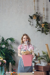 Picture of florist woman with bouquet in box against background of indoor plants