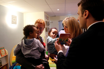 French President Emmanuel Macron shows a book to children as his wife Brigitte Macron holds a child in her hands during a visit to unveil an autism plan at the Rouen hospital