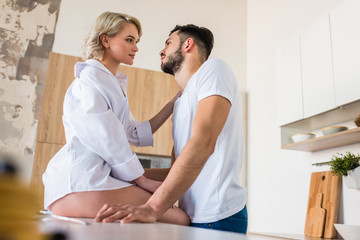 side view of sensual young couple looking at each other in kitchen at morning