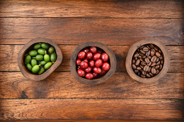 Coffee beans and fresh berries beans on wooden background