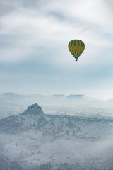 Hot air balloon and Cappadocia aerial view during winter