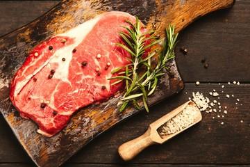 Raw steak on a wooden cutting board