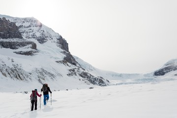Couple walking on a snow capped mountain