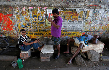 A man combs his hair under a flyover on the outskirts of Kolkata