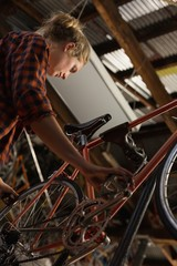Female mechanic examining a bicycle