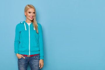 Blond Woman In Turquoise Blouse Is Posing With Hand In Pocket And Smiling