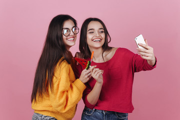 Two smiling girls take selfie on their phones posing with lollipops