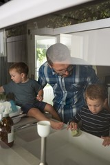 Father and son cleaning sink in kitchen