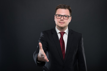 Portrait of business man wearing black suit offering hand shake.