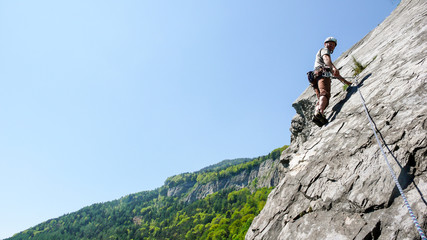 mountain guide rock climber on a slab limestone climbing route in the Alps of Switzerland on a beautiful day