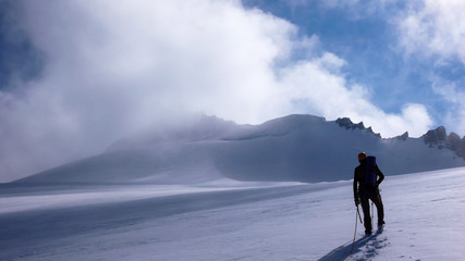 male mountain guide on a flat and large glacier looking towards a mountain peak in the clouds and his goal for the day