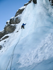 male ice climber in a blue jacket on a steep ice fall in winter