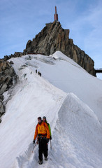 mountain guide and a male client on a snow ridge heading down from a high summit in the French Alps near Chamonix