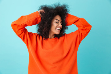 Colorful portrait of smiling woman in red shirt looking aside and touching her dark curly hair, isolated over blue background