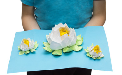 Very beautiful origami in child's hands: three white lotuses on the lake