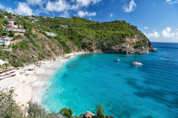 Harbor with sand beach, blue sea and mountain landscape in gustavia, st.barts. Summer vacation on tropical beach. Recreation, leisure and relax concept. Wanderlust and travel with adventure.