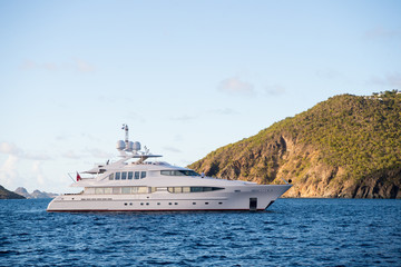 Yacht at sea coast on sunny blue sky in gustavia, st.barts. Yachting and sailing adventure. Luxury travel and voyage on boat. Summer vacation on tropical island. Water transport and marine vessel