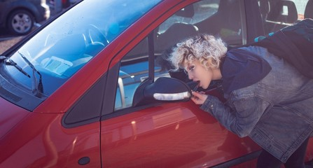 Woman looking on rear view mirror of car
