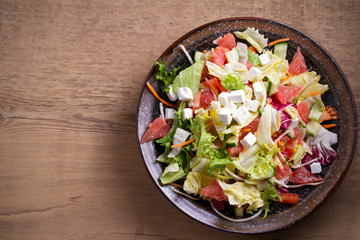 Healthy vegetarian food: citrus grapefruit, tomato, lettuce and cucumber salad with feta cheese in bowl on wooden table. overhead, horizontal