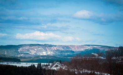 Fototapeta Stone-pit in winter mountain landscape under blue cloudy sky. Winterberg, Germany.
