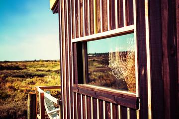 Net haning inside window of fisherman hut