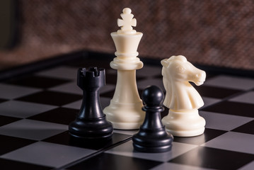 the abstract image of the staunton chess set such as king, knight, rook, pawn placed on chess board and brown texture backdrop. the comcept of strategy, victory, business, win, games, intelligence.