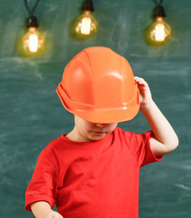 Small boy in orange helmet standing under bright lightbulbs. Kid hiding his face beneath headwear.