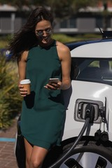 Woman using mobile phone while charging electric car at service