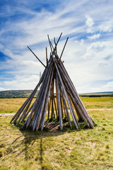 Wood carcass of wigwam on the field between mountains. Adventure concept. Outdoor photo.