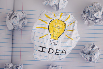 Drawing of a light bulb with word Idea on crumpled paper ball