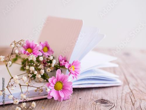 Rosa und weiße Blumen auf einem Notizbuch auf einem grauen Holztisch ...