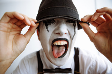 The clown mime shows the tongue and pulls the hat over his eyes. Mime.