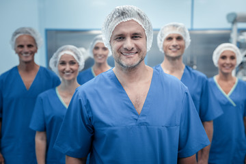 Team of surgeons. Smart experienced male surgeon standing in front of his team and looking at you while wearing uniform